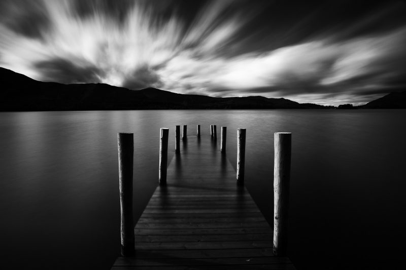 black and white landscape showing a pier, mountains and clouds