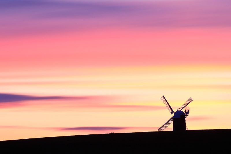 Windmill silhouette against pink sky