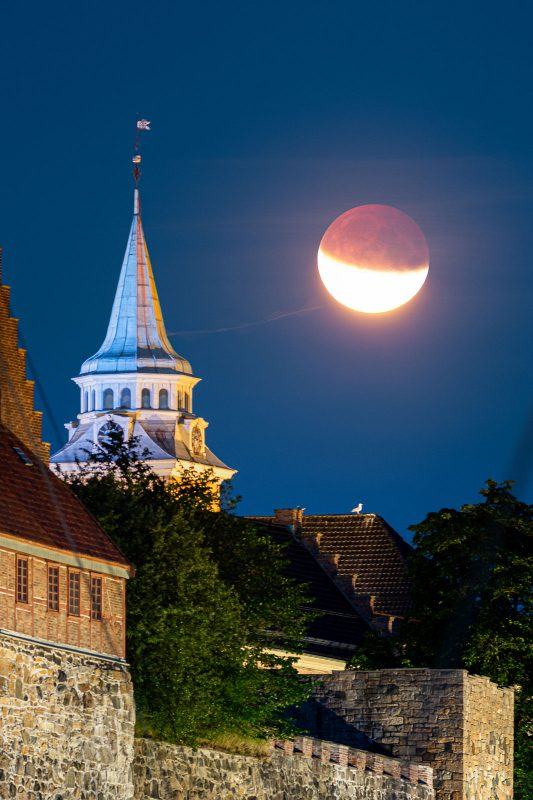 The partially eclipsed Moon next to Akershus Festning