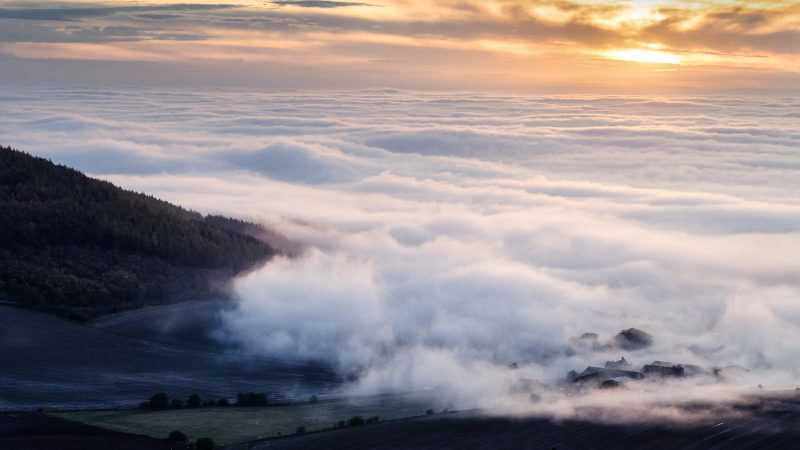 landscape photo overlooking hills covered in thick mist