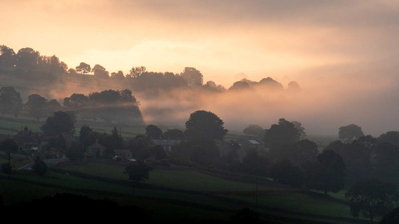 Countryside landscape at dawn, covered in mist