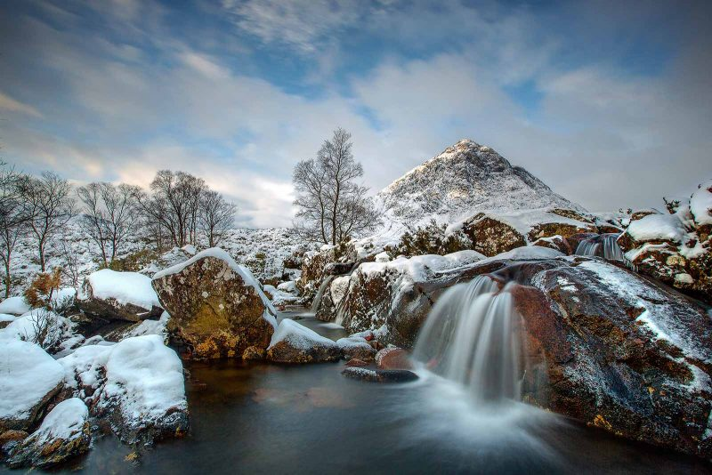 a partially frozen waterfall with plenty of background interest including mountain