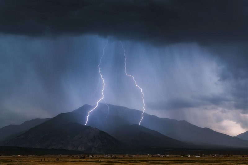 two bolts of lightning strike a mountain in a storm