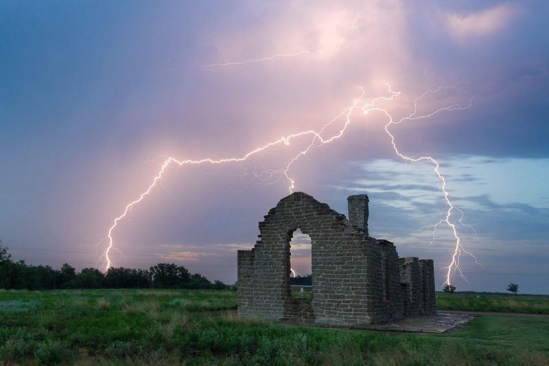 lightning bolts strike around a ruined building