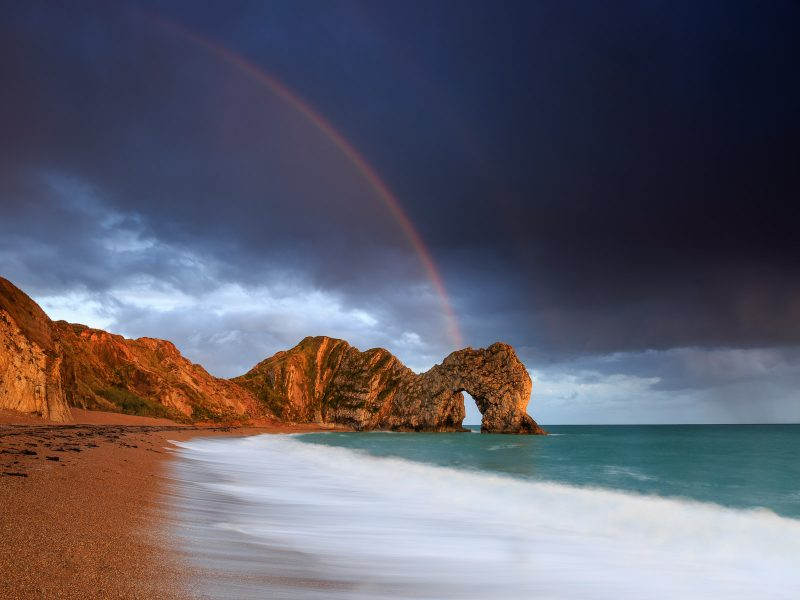 A clearing shower over Durdle Door in late afternoon light
