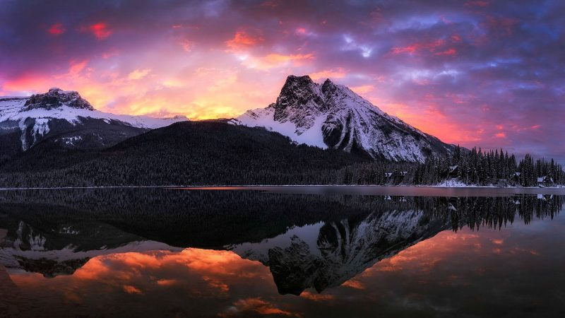 A mountain reflects into a lake with the sun setting behind it