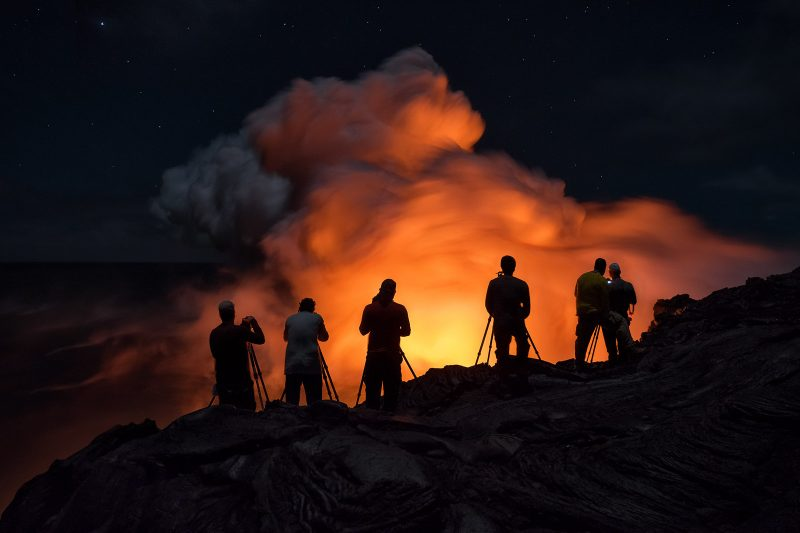 Photographers stand in front of volcano