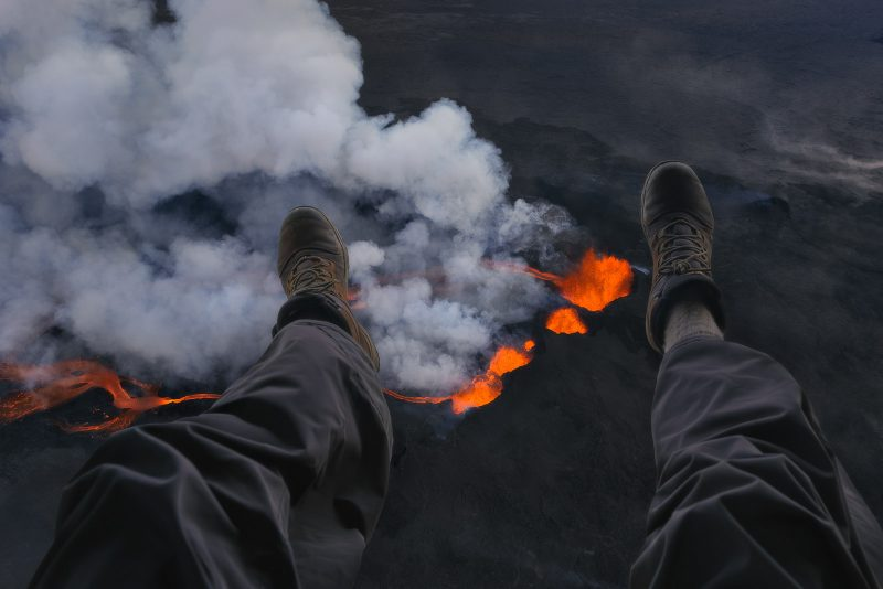 photographer's legs hanging above a volcano