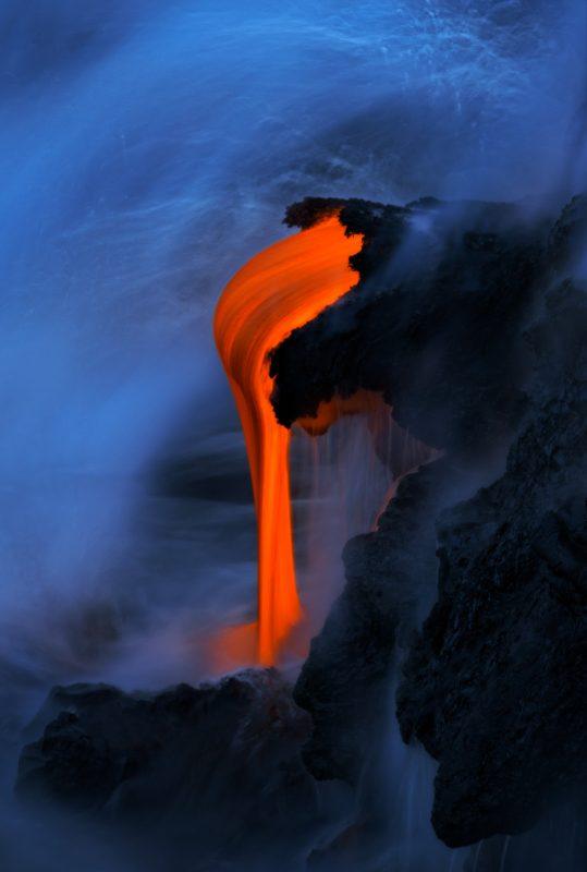 Glowing lava drips into the sea