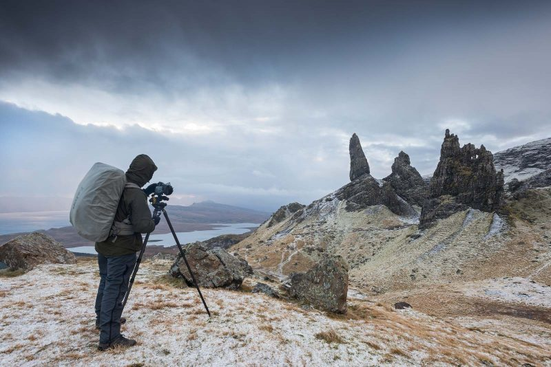Photographer in coat photographing landscape
