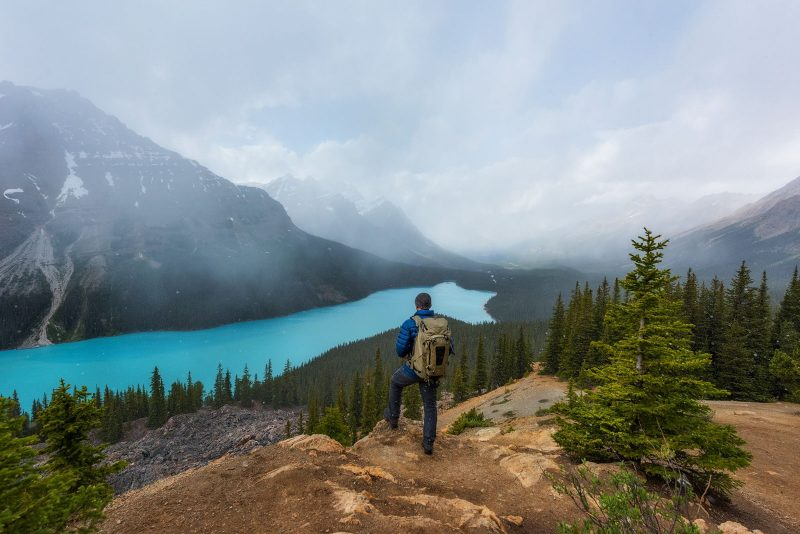 Travel photograph of man looking over a lake and mountains