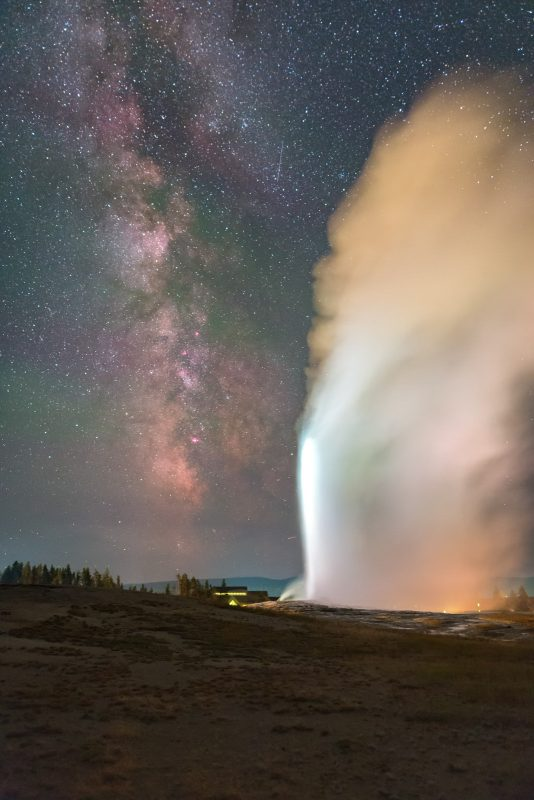 Old Faithful geyser in Yellowstone National Park, under the Milky Way