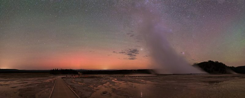 Colorful airglow and pink-orange Northern Lights are visible in this panorama of the night sky taken in Yellowstone National Park