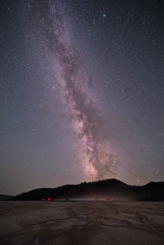 Milky Way is very prominent in the night sky above Grand Prismatic Spring in Yellowstone National Park