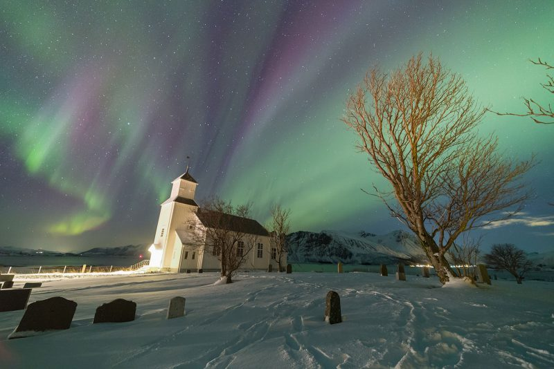 Colorful Aurora lights up the sky above the church