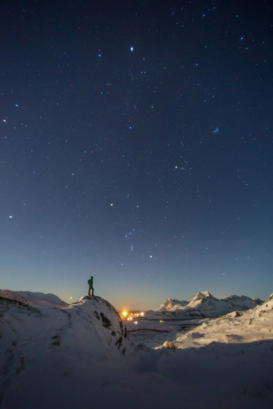 Man on mountain looks at night sky. Shot at 17mm.