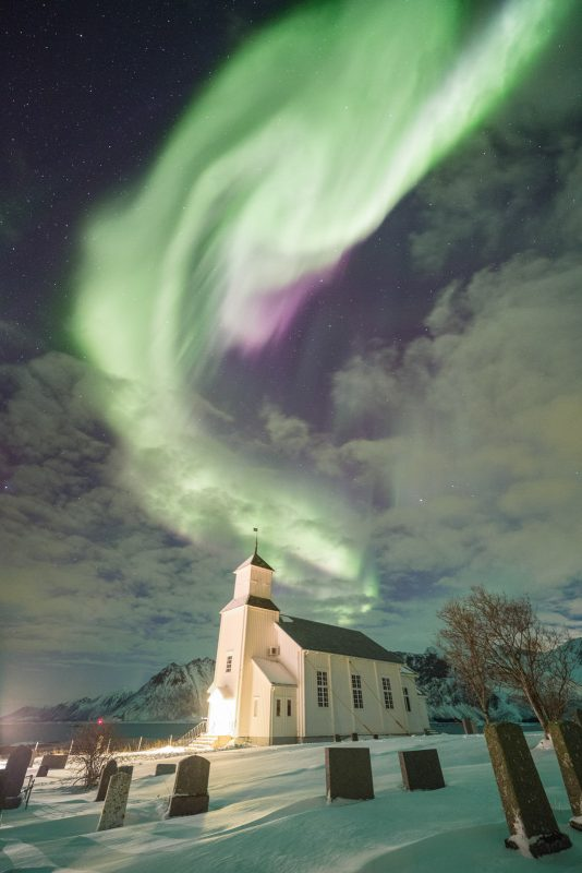 Colorful Aurora lights up the sky above the church on the island of Gimsøya, Lofoten, Norway.