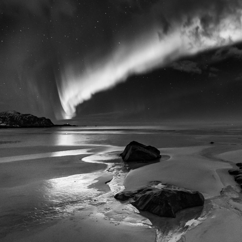 A black and white view of the Northern Lights above the beach at Flakstad.