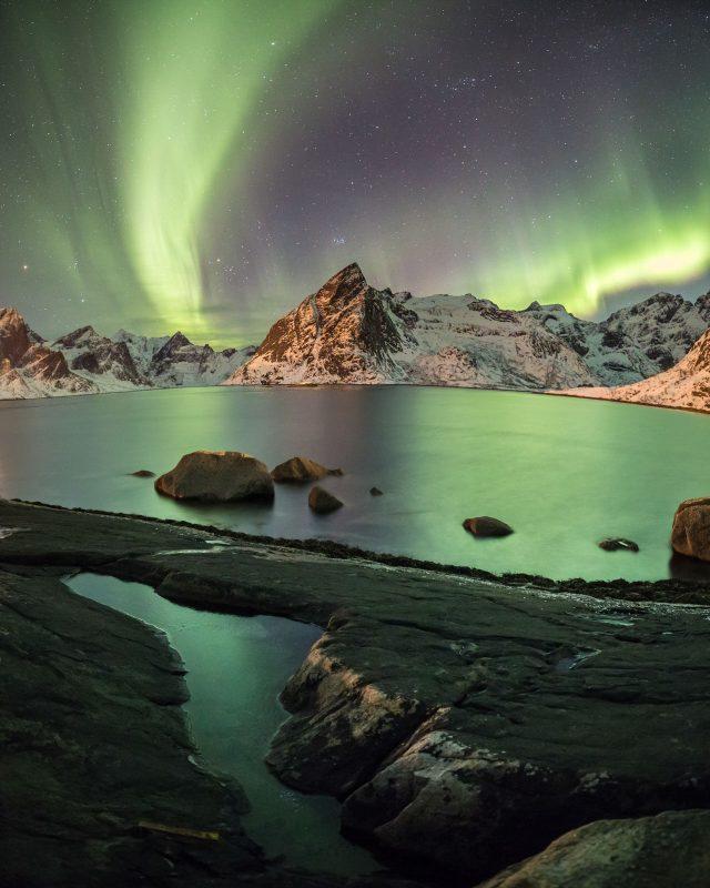 Aurora Borealis shines bright above mount Olstind and Reinefjord, next to Reine, Lofoten Islands, Norway