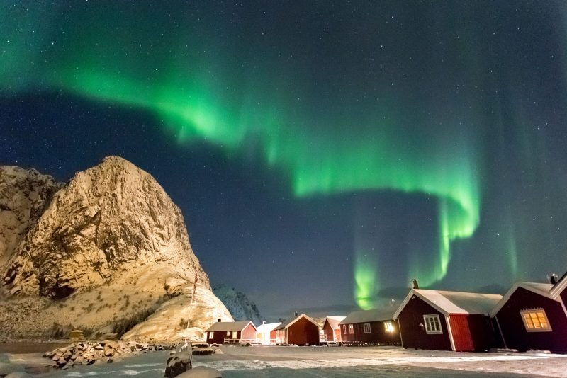 Aurora Borealis above a snow covered traditional village in the Lofoten Islands, Norway.