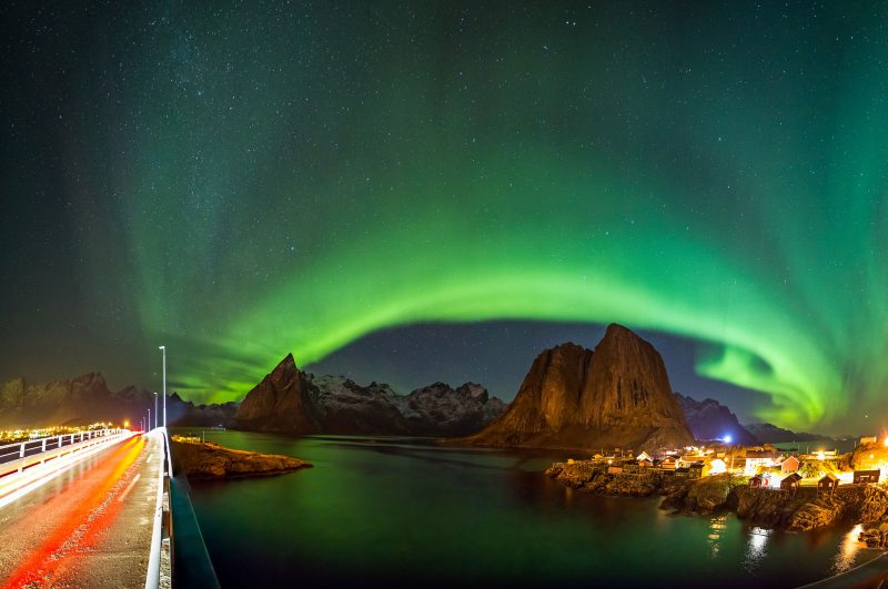 Panorama of bright Northern Lights above the village of Hamnoy, Lofoten Islands, Norway.